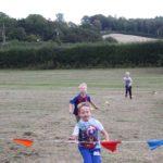 Children running towards a ribbon in a field