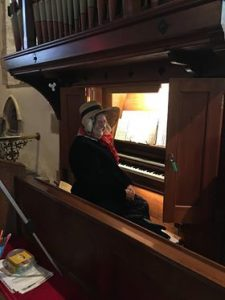 Woman in bonnet playing the organ
