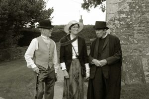 Black and white photo of two men and a woman in victorian costumes