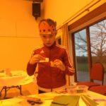 A boy wearing a paper crown
