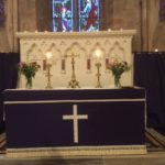 The altar and a stained glass window lit with candles