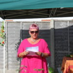 Woman in pink reading from a sheet of paper