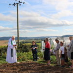 The vicar talking to a group of people on the allotments