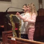 Two children standing at a lectern with tinsel