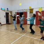 Children tossing pancakes in the village hall