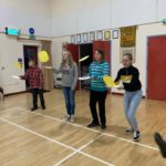 Four children tossing pancakes in the village hall
