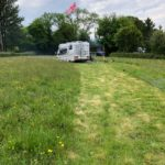 Flag on pole with white campervan in a field