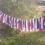 Red, white and blue material hanging on a washing line outside a stone house