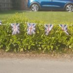 Union jack bunting on a green hedge with a blue car behind