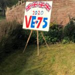Poster with pictures of Union Jacks and the words VE Day 2020 on a stand in front of a wall