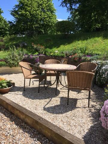 Garden table and four chairs in front of grass bank and a tree