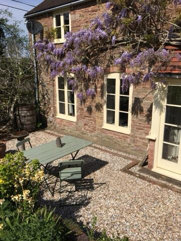 Stone house covered in purple wisteria