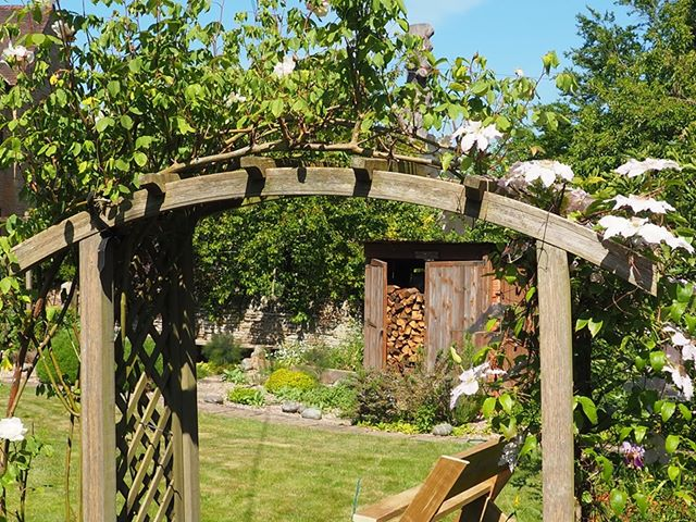 Wooden arch, lawn and log store full of logs