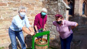 Three women using a press to make apple juice