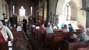 Members of the congregation and the vicar inside the church