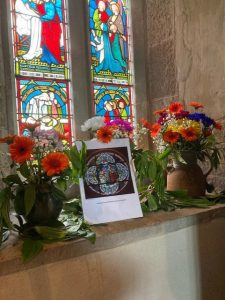 orange flowers in front of a stained glass window